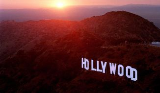 FILE- This June 30, 1999 file photo shows the sun setting behind mountains as the Hollywood sign overlooks Los Angeles. For a century and a half California has been a destination for every conceivable sort of adventurer. (AP Photo/Reed Saxon, File)