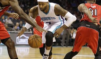 Charlotte Hornets' Mo Williams, middle, looses the dribble as he tries to drive past Toronto Raptors' Amir Johnson, left and Terrence Ross, right, during the first half of an NBA basketball game in Charlotte, N.C., Friday, March 6, 2015. (AP Photo/Bob Leverone)