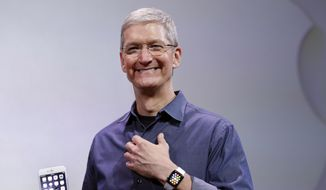 In this Sept. 9, 2014, file photo, Apple CEO Tim Cook, holding an iPhone 6 Plus and wearing an Apple Watch, discusses the new products during an event in Cupertino, Calif. (AP Photo/Marcio Jose Sanchez, File)