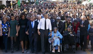 """President Barack Obama, center, walks as he holds hands with Amelia Boynton Robinson, who was beaten during """"Bloody Sunday,"""" as they and the first family and others including Rep. John Lewis, D-Ga,, left of Obama, walk across the Edmund Pettus Bridge in Selma, Ala. for the 50th anniversary of """"Bloody Sunday,"""" a landmark event of the civil rights movement, Saturday, March 7, 2015. From front left are Marian Robinson, Sasha Obama. first lady Michelle Obama. Obama, Boynton and Adelaide Sanford, also in wheelchair. (AP Photo/Jacquelyn Martin)"""