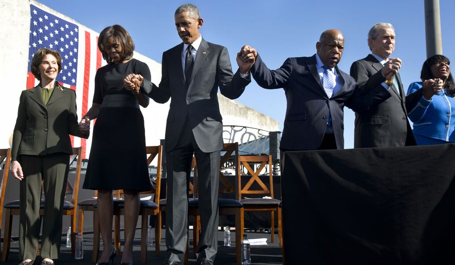 """Former first lady Laura Bush, left, first lady Michelle Obama, President Barack Obama, Rep. John Lewis, D-Ga., former President George W. Bush, and Rep. Terri Sewell, D-Ala., hold hands during a prayer after the president's speech by the Edmund Pettus Bridge in Selma, Ala., on the 50th anniversary of """"Bloody Sunday,"""" a landmark event of the civil rights movement, Saturday, March 7, 2015. (AP Photo/Jacquelyn Martin)"""