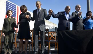 "Former first lady Laura Bush, left, first lady Michelle Obama, President Barack Obama, Rep. John Lewis, D-Ga., former President George W. Bush, and Rep. Terri Sewell, D-Ala., hold hands during a prayer after the president's speech by the Edmund Pettus Bridge in Selma, Ala., on the 50th anniversary of ""Bloody Sunday,"" a landmark event of the civil rights movement, Saturday, March 7, 2015. (AP Photo/Jacquelyn Martin)"