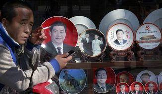 In this March 4, 2015 photo, a man smokes near the souvenir plates bearing images of Chinese President Xi Jinping on display together with China's former presidents at a shop near Tiananmen Square in Beijing. Barely two years into office, Xi has attracted an extraordinary degree of attention to his public persona that veers perilously close to a full-blown personality cult. Such a phenomenon has not seen since the days of Mao Zedong, with successors wary of the turmoil his leadership unleashed and generally favoring a dry, rule-by-consensus approach. (AP Photo/Andy Wong)