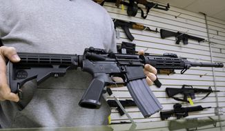 John Jackson, co-owner of Capitol City Arms Supply in Springfield, Illinois, shows off an AR-15 assault rifle. The Second Amendment Foundation will launch a nationwide TV and radio campaign Monday aimed at exposing legal holes in President Obama's executive actions to ban ammunition commonly used in AR-15s. (Associated Press)