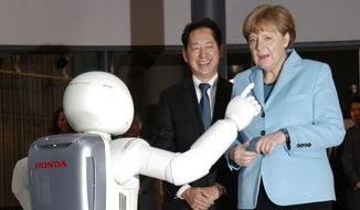 "German Chancellor Angela Merkel, right, watches Honda Motor Co.'s interactive robot Asimo demonstrate, along with the National Museum of Emerging Science and Innovation ""Miraikan"" Chief Executive Director Mamoru Mori during her visit to the the museum in Tokyo, Monday, March 9, 2015. Merkel is in Japan on Monday and Tuesday as part of a series of bilateral meetings with G-7 leaders ahead of a June summit in Germany. (AP Photo/Shizuo Kambayashi)"