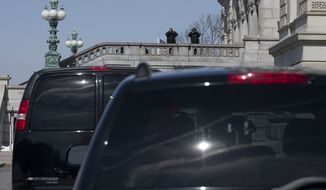 Members of the Secret Service keep watch as the motorcade that delivered President Barack Obama and his daughters Sasha and Malia is parked, Sunday, March 8, 2015, in Washington, in front of the Library of Congress where the president took his daughters to view the original manuscript of President Abraham Lincoln's Second Inaugural Address, which the Library of Congress put on display to commemorate the 150th anniversary of its delivery. (AP Photo/Carolyn Kaster)