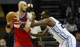 Washington Wizards center Marcin Gortat, left, of Poland, looks to pass against Charlotte Hornets center Al Jefferson in the first half of an NBA basketball game Monday, March 9, 2015, in Charlotte, N.C. The Wizards won 95-69. (AP Photo/Nell Redmond)