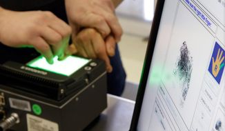 In this March 3, 2015 photo, a person arrested by Immigration and Customs Enforcement is electronically  fingerprinted, at their headquarters, in New York, after a series of early-morning raids. Immigrant and Customs Enforcement say an increasing number of cities and counties across the United States are limiting cooperation with the agency and putting its officers in dangerous situations as they track down foreign-born criminals. Instead, more of its force is out on the streets, eating up resources and conducting investigations because cities like New York and states like California have passed legislation that limits many of the detention requests issued by immigration authorities.  (AP Photo/Richard Drew) **FILE**