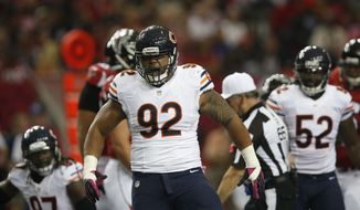Chicago Bears defensive tackle Stephen Paea (92) reacts to a helping sack Atlanta Falcons quarterback Matt Ryan (2) during the first half of an NFL football game, Sunday, Oct. 12, 2014, in Atlanta. (AP Photo/Brynn Anderson )