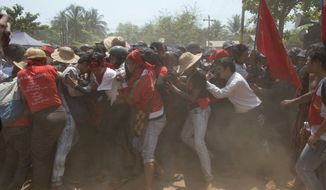 Student protesters struggle to break a police human-chain during a student protester ahead of a crackdown in Letpadan, 140 kilometers (90 miles) north of the country's main city Yangon, Myanmar, Tuesday March 10, 2015. (AP Photo/Gemunu Amarasinghe)