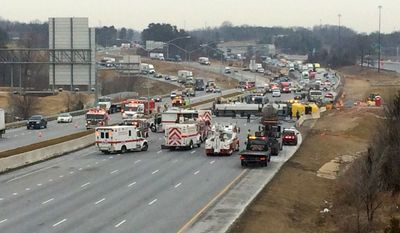 This handout photo provided by the Prince George's County, Md., Fire Department shows an overturned tanker on Interstate 95 in Laurel, Md., Tuesday, March 10, 2015. Interstate 95 was closed in both directions in the Laurel area after officials say a tanker truck carrying bio-diesel fuel overturned across southbound lanes. The tanker overturned Tuesday morning in southbound lanes south of state Route 198. Local media are showing aerial shots of the tanker lying across four lanes of traffic and pushing into jersey barrier walls along the median. (AP Photo/Assistant Fire Chief Paul Gomez, Prince George's County, Md., Fire Department)