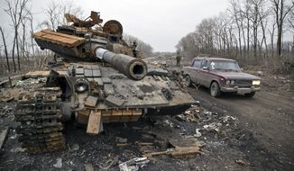 A car passes a destroyed tank abandoned on the road at a former Ukrainian army checkpoint that was overran last month by Russia-backed separatists during the offensive for Debaltseve, outside the city of Chornukhyne, Ukraine, near Debaltseve on March 2, 2015. The struggle for the strategic rail hub, Debaltseve, a sleepy town with a prewar population of 25,000 people, left the town in ruins and became one of the darkest pages in the ongoing conflict in eastern Ukraine, which has already killed more than 6,000 people. (Associated Press) **FILE**