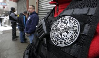 In this March 2, 2015 photo, Immigration and Customs Enforcement officers try to gain entry to an apartment building, in the Bronx borough of New York, during a series of early-morning arrests. Immigrant and Customs Enforcement say an increasing number of cities and counties across the United States are limiting cooperation with the agency and putting its officers in dangerous situations as they track down foreign-born criminals. Instead, more of its force is out on the streets, eating up resources and conducting investigations because cities like New York and states like California have passed legislation that limits many of the detention requests issued by immigration authorities.  (AP Photo/Richard Drew)