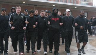 The University of Oklahoma football team and coaches line up wearing all black in the Everest Training Center in protest of the Sigma Alpha Epsilon fraternity at the University of Oklahoma on Monday, March. 9, 2015. The Sigma Alpha Epsilon fraternity has been banned from campus after several members tof the fraternity took part in a racist chant caught on video. (AP Photo/Tulsa World, Nick Oxford)  ONLINE OUT; KOTV OUT; KJRH OUT; KTUL OUT; KOKI OUT; KQCW OUT; KDOR OUT; TULSA OUT; TULSA ONLINE OUT