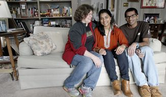 n this Jan. 23, 2015 photo, Diane DeMers, of DeKalb, Ill., sits at home with her adopted children Pooja Ballantine, center, and Keerti Ballantine. DeMers made two trips to India to adopt the two. Pooja, now 22, was adopted in 2002 at the age of 10, and Keerti, 21, was adopted in 1996 when he was two. American citizens adopt thousands of international children every year, according to data from the U.S. State Department. (AP Photo/Daily Chronicle, Monica Synett) CHICAGO TRIBUNE OUT, MANDATORY CREDIT