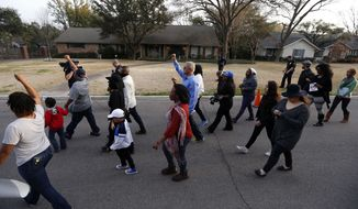 About two-dozen protesters march outside the family home, background, of a former University of Oklahoma Sigma Alpha Epsilon fraternity member Parker Rice, Wednesday, March 11, 2015, in Dallas. Rice and several other fraternity members were seen on video chanting a racist song. (AP Photo/Brandon Wade)