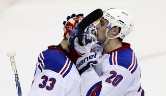 New York Rangers goalie Cam Talbot (33) gets a kiss on the helmet from left wing Chris Kreider (20) after an NHL hockey game against the Washington Capitals, Wednesday, March 11, 2015, in Washington. The Rangers won 3-1. (AP Photo/Alex Brandon)