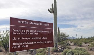 A sign warns visitors of smuggling and illegal immigration at the Organ Pipe Cactus National Monument in Arizona, in this Oct. 30, 2014, file photo. For over a decade, armed drug traffickers were so prevalent in this vast desert monument that visitors were barred from entering more than half of it. (AP Photo/Astrid Galvan) ** FILE **