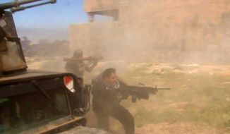 In this still image taken from video, soldiers fire toward a target in Tikrit, Iraq on Wednesday, March 11, 2015. (AP Photo)