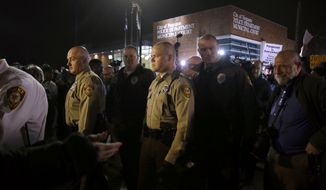 Officers from the St. Louis Police Department walk through a crowd of protesters outside the Ferguson Police Department, Thursday, March 12, 2015, in Ferguson, Mo. Two police officers were shot early Thursday morning in front of the Ferguson Police Department during a protest following the resignation of the city's police chief in the wake of a U.S. Justice Department report. (AP Photo/Jeff Roberson)