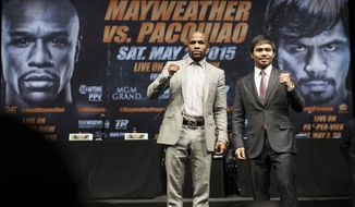 Floyd Mayweather Jr., left, and Manny Pacquiao strike their poses after a news conference Wednesday, March 11, 2015, in Los Angeles. Mayweather and Pacquiao are scheduled to fight in a boxing bout May 2 in Las Vegas. (AP Photo/The Orange County Register, Ed Crisostomo)