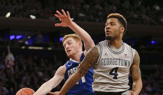 Georgetown's D'Vauntes Smith-Rivera (4) passes away from Creighton's Geoffrey Groselle (41) during the first half of an NCAA college basketball game in the in the quarterfinals of the Big East Conference tournament, Thursday, March 12, 2015, in New York. (AP Photo/Frank Franklin II)
