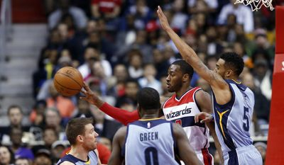 Washington Wizards guard John Wall (2) passes between Memphis Grizzlies guard Beno Udrih (19), forward JaMychal Green (0) and guard Courtney Lee (5) during the first half of an NBA basketball game Thursday, March 12, 2015, in Washington. (AP Photo/Alex Brandon)