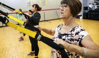 In this Feb. 5, 2015 photo, Mary Magee-Huth teaches a fitness class at the Inwood Athletic Club in Joliet Ill. After the birth of her first daughter, Magee-Huth, who was 21 at the time, had a stroke. Then at 39, six years after the birth of her second daughter, she was on A dialysis, disability and a transplant list. These were just some of the consequences of the Type 1 diabetes she had battled since her diagnosis in 1970, at age 11. Fifteen years ago she underwent had a kidney-pancreas transplant. (AP Photo/The Herald-News, Lathan Goumas) CHICAGO TRIBUNE OUT, MANDATORY CREDIT