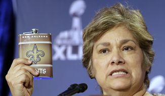U.S. Immigration and Customs Enforcement Director Sarah Saldana holds up a counterfeit flask during a counterfeit ticket and merchandise news conference for NFL Super Bowl XLIX football game in Phoenix. (AP Photo/Morry Gash, File)