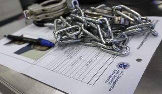 In this March 3, 2015 photo, handcuffs and chains sit on the paperwork of a person arrested by Immigration and Customs Enforcement officers after a series of early-morning arrests in New York. Immigrant and Customs Enforcement say an increasing number of cities and counties across the United States are limiting cooperation with the agency and putting its officers in dangerous situations as they track down foreign-born criminals. (AP Photo/Richard Drew)