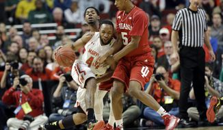 Maryland's Dez Wells (44), left, is defended by Indiana's Troy Williams (5) in the first half of an NCAA college basketball game in the quarterfinals of the Big Ten Conference tournament in Chicago, Friday, March 13, 2015. (AP Photo/Nam Y. Huh)