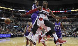 Washington Wizards guard John Wall (2) passes the ball under the basket as he is covered by Sacramento Kings guard Ben McLemore (23) in the first half of an NBA basketball game Saturday, March 14, 2015, in Washington. (AP Photo/Alex Brandon)