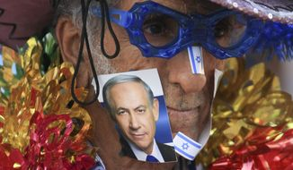 A supporter of Israeli Prime Minister Benjamin Netanyahu, on the photo, waits for his campaign rally to start in Tel Aviv, Israel, Sunday, March 15, 2015, two days ahead of parliament elections. Netanyahu seeks his fourth term as prime minister. (AP Photo/Ariel Schalit)