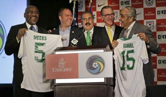 New York Congressmen Charles Rangel, right, and Gregory Meeks, left, are presented with New York Cosmos jerseys during a news conference in New York, Monday, March 16, 2015. Also pictured are New York Cosmos head coach Giovanni Savarese, second from left, sportscaster Fernando Fiore, center, and former Cosmos player Shep Messing, second from right. The New York Cosmos will be the first professional American sports team to play on Cuban soil in 16 years; the match against the Cuba National Team will take place on June 2, 2015, in Havana, Cuba. (AP Photo/Seth Wenig)