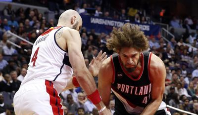 Washington Wizards center Marcin Gortat (4), from Poland, reaches for the ball as Portland Trail Blazers center Robin Lopez (42) drives to the basket in the first half of an NBA basketball game Monday, March 16, 2015, in Washington. (AP Photo/Alex Brandon)