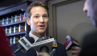 In this Feb. 6, 2015 photo, Rep. Aaron Schock, R-Ill., answers questions from the media as he returns to Peoria, Ill., to speak to the Peoria County Farm Bureau. A shell company linked to Schock paid a political donor $300,000 last year for a commercial property in Peoria then took out a $600,000 mortgage for the property from a local bank run by other donors, Illinois state and county records show.   (AP Photo/Journal Star, Fred Zwicky)