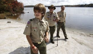 In this Oct. 3, 2009 photo, Tenderfoot Scout Bradley Corr, 11, left, his father Warren Corr, Troop 29 committee member, right, and his grandfather Ted Corr, who is Unit Commissioner with the Forks of the Delaware district of the Minis Trails Council walk along the shore of Stillwater Lake at Boy Scout camp at Camp Minsi in Pocono Summit, Pa. As the Boy Scouts of America heads toward its 100th anniversary in February, its first century adds up to a remarkable saga, full of achievement, complexity and contradiction. On one hand, no other U.S. youth organization has served as many boys, an estimated 112 million over the years. On the other hand, in both the courts and the public arena, the BSA has doggedly defended its right to discriminate, excluding gays and atheists from its ranks, and overriding requests from some local units to soften those policies. (AP Photo/Carolyn Kaster)