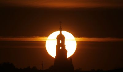 An Orthodox church is silhouetted during sunset in the village of Mozoli, 30 miles northwest of the capital,  Minsk, Belarus, Monday, March 16, 2015. (AP Photo/Sergei Grits)
