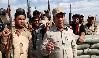 Hakim al-Zamili, a parliament member and head of Security and Defense Committee, right, visits the front line during a battle against Islamic State militants in Tikrit, 130 kilometers (80 miles) north of Baghdad, Iraq, Monday, March 16, 2015. The offensive to retake Saddam Hussein's hometown of Tikrit began March 2. The city is one of the largest held by the Islamic State militants on the road connected Baghdad and Mosul. Iraqi Interior Minister Mohammed Salem al-Ghabban said Monday that the campaign had halted temporarily to allow civilians in the city to evacuate and to enable troops to clear roadside bombs planted by the extremists. (AP Photo/Khalid Mohammed)