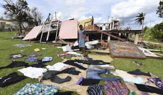In this Monday, March 16, 2015, photo, clothes are seen laid out to dry as Adrian Banga surveys his destroyed house in Vanuatu's capital Port Vila. Aid has begun arriving in the storm-hit nation's capital following Cyclone Pam, but contact has still not been made with some of its more remote islands. (AP Photo/Dave Hunt, Pool)