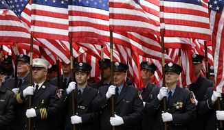 Members of the FDNY carry American flags during the St. Patrick's Day Parade in New York, Tuesday, March 17, 2015. (AP Photo/Seth Wenig)