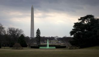 """With the Washington Monument and Jefferson Memorial in the background, the fountain on the South Lawn of the White House in Washington, is dyed green for St. Patrick's Day, Tuesday, March 17, 2015, prior to President Barack Obama's motorcade taking the president to Capitol Hill for a """"Friends of Ireland"""" luncheon. (AP Photo/Jacquelyn Martin)"""