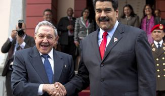 Cuba's President Raul Castro, left, shakes hands with Venezuela's President Nicolas Maduro in front of the press after arriving to Miraflores presidential palace for an emergency ALBA meeting in Caracas, Venezuela, Tuesday, March 17, 2015. The Venezuelan-led ALBA bloc of leftist regional governments is expected to express support for Venezuela's position that its sovereignty is being violated by U.S. attempts to destabilize the country. (AP Photo/Ariana Cubillos)