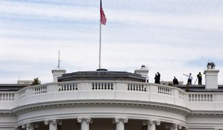 """Uniformed Secret Service agents patrol the top of the White House as seen from the South Lawn of the White House in Washington, Tuesday, March 17, 2015. According to the Secret Service a letter sent to the White House tentatively tested positive for cyanide. The letter was received at an off-site mail screening facility on March 16 and additional testing Tuesday returned a """"presumptive positive"""" for cyanide. (AP Photo/Jacquelyn Martin)"""