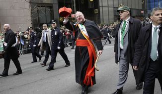 The Grand Marshall of the St. Patrick's Day Parade, Archbishop Timothy Dolan, walks past protesters during the St. Patrick's Day Parade in New York, Tuesday, March 17, 2015. A group of people along the parade route were protesting the exclusion of LGBT groups from the parade. (AP Photo/Seth Wenig)