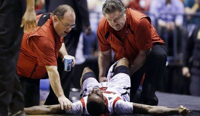 FILE - In this March 31, 2013, file photo, trainers check on Louisville guard Kevin Ware after he injured his leg during the first half of the Midwest Regional final against Duke in the NCAA college basketball tournament in Indianapolis. The last time Kevin Ware played in the NCAA Tournament, he left the court on a stretcher, his right leg gruesomely broken in a freak incident that left his teammates in tears.  He's looking to leave a much different impression this time around. (AP Photo/Michael Conroy, File)
