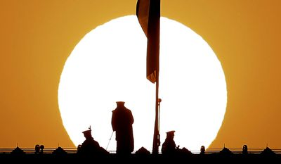 AP10ThingsToSee - As the sun rises, Chinese paramilitary policemen watch over Tiananmen Square from a rooftop across from the Great Hall of the People ahead of the closing ceremony of the annual National People's Congress in the hall in Beijing on Sunday, March 15, 2015. (AP Photo/Andy Wong)