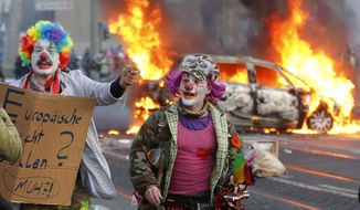 Demonstrators dressed as clowns pass by a burning police car Wednesday, March 18, 2015 in Frankfurt, Germany. Blockupy activists try to blockade the new headquarters of the ECB to protest against government austerity and capitalism.  (AP Photo/Michael Probst)