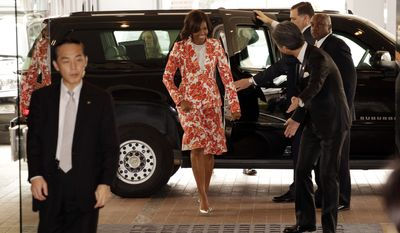 U.S. first lady Michelle Obama, center, is escorted by staff members at Iikura Guest House in Tokyo, Thursday, March 19, 2015. Obama is visiting Japan and Cambodia, who are among Asia's richest and poorest nations, to highlight cooperation on helping girls finish their educations.(AP Photo/Eugene Hoshiko)