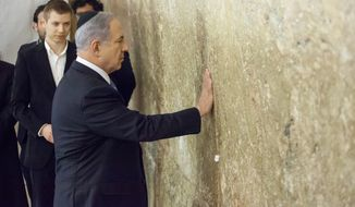 Israeli Prime Minister Benjamin Netanyahu prays at the tunnel section of the Western Wall in Jerusalem Wednesday, March 18, 2015. Netanyahu's right-wing Likud Party scored a resounding victory in Israel's election, final results showed Wednesday, a stunning turnaround after a tight race that had put his lengthy rule in jeopardy. (AP Photo/Emeil Salman)